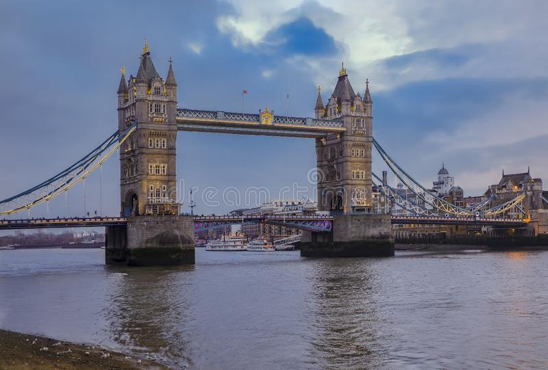 View of the London city skyline at sunset with Tower Bridge on Thames river in England, United Kingdom. View of the London city skyline at sunset on a cloudy day stock photo