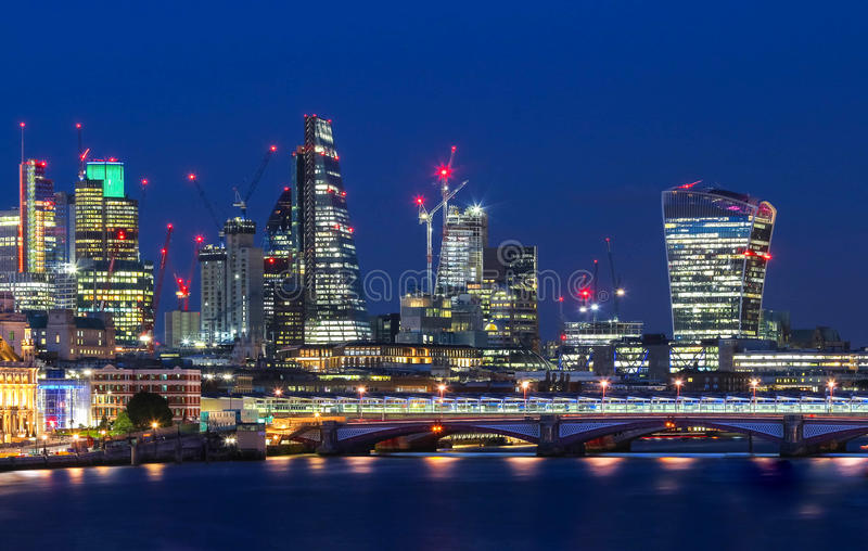 The view of London`s city hall and modern skyscrapers at night stock photography