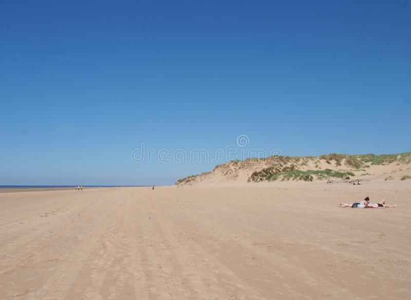 A view of the long sandy beach in formby merseyside on a bright summer day with blue sky with people sunbathing and grass covered stock photography
