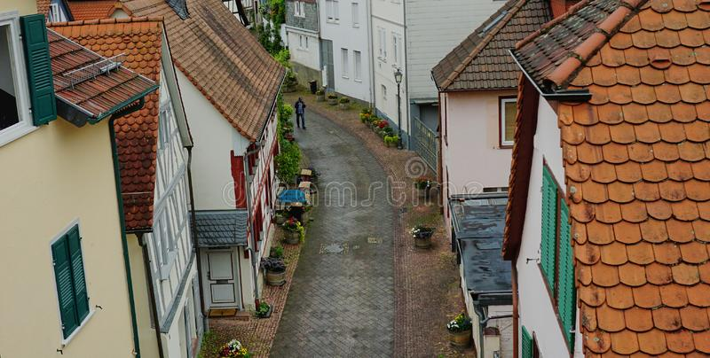 Medieval Street Scene in Bad Homburg, Germany. View looking down from a bridge onto a narrow old street with quaint homes with tiled roofs, while solitary man stock image