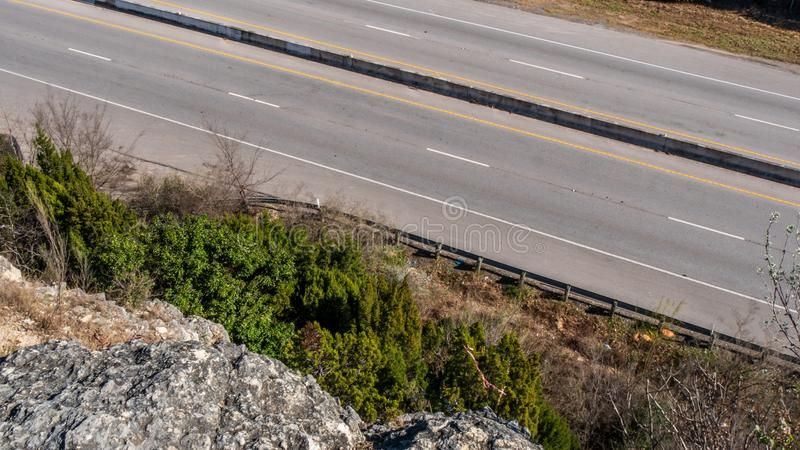View looking down at an empty road from a cliff side stock images