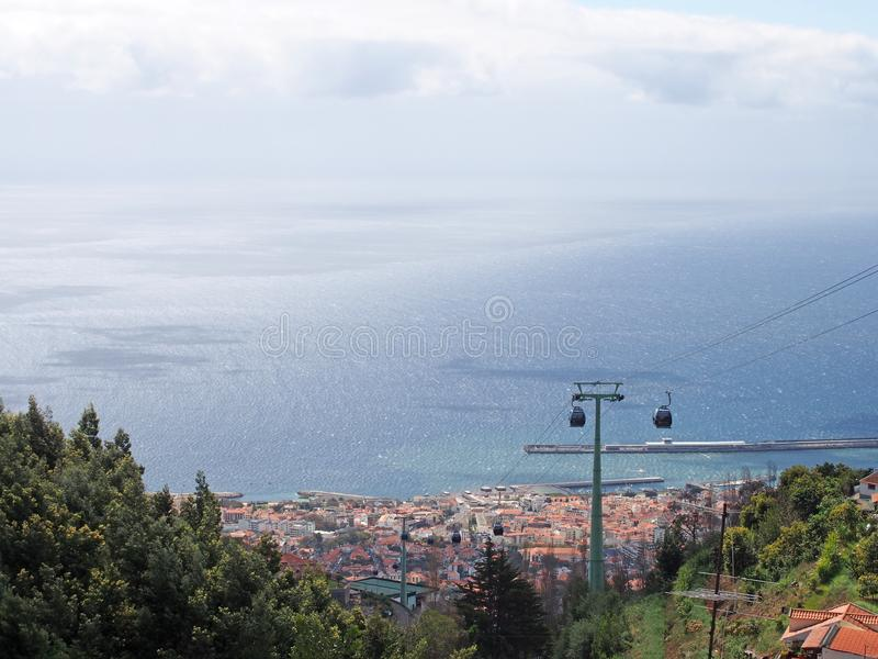 View looking down on funchal madeira taken from monte with the cable car from the city and a bright blue sunlit sea. A view looking down on funchal madeira taken royalty free stock images