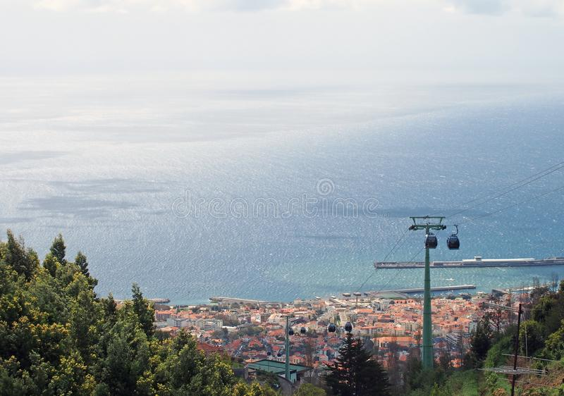 View looking down on funchal madeira taken from monte with the cable car from the city and a bright blue sunlit sea. A view looking down on funchal madeira taken royalty free stock image