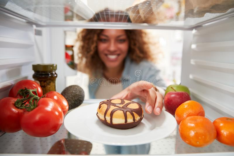 View Looking Out From Inside Of Refrigerator As Woman Opens Door And Reaches For Unhealthy Donut stock image