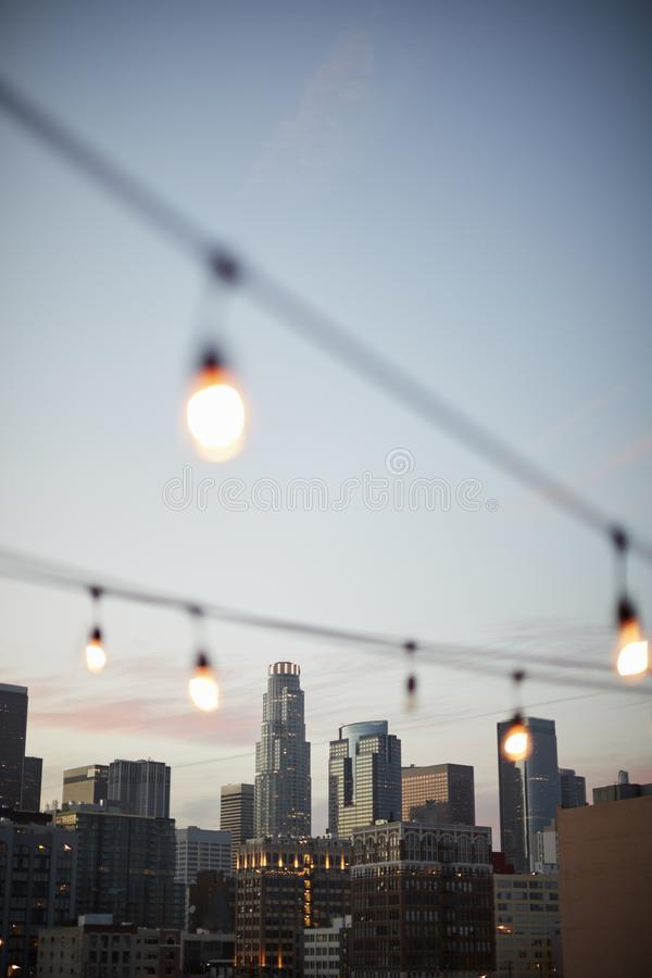 View Of Los Angeles Skyline At Sunset With String Of Lights In Foreground stock photos