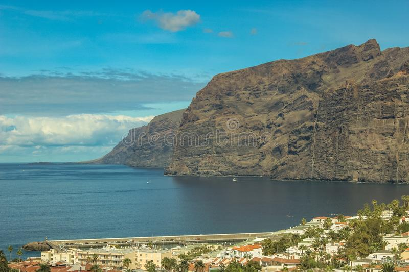 View of the Los Gigantes port and volcanic cliffs on the west coast of the Tenerife island. Sunny day, clear blue sky with little stock photos