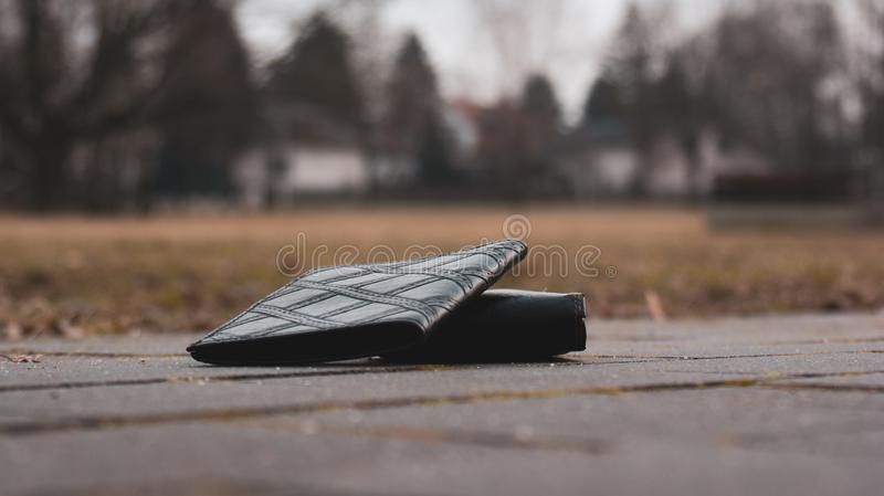 Closeup on wallet and document case. View at lost documents and wallet lying on paving, black leather case and billfold stock image