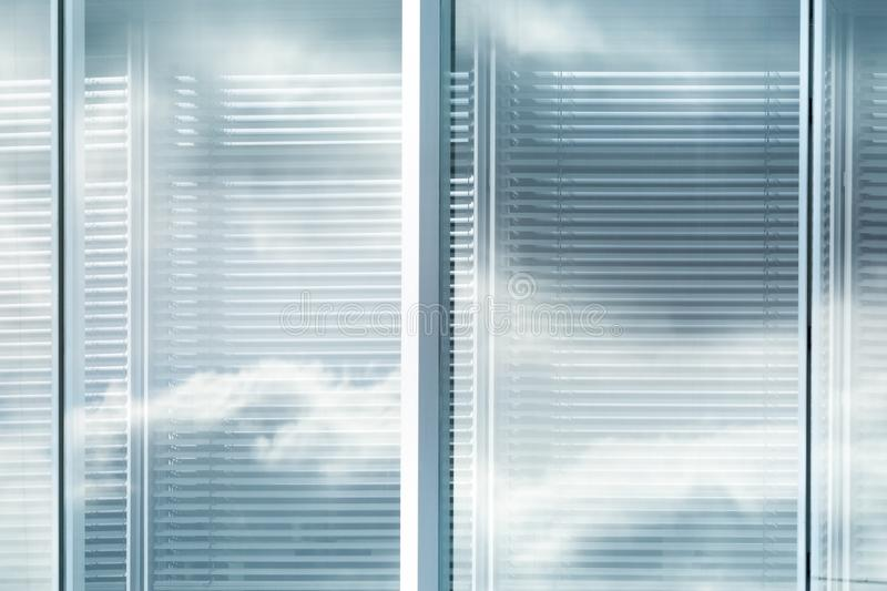 View of louvers window of modern office building with reflection of sky with clouds, blurred effect stock images