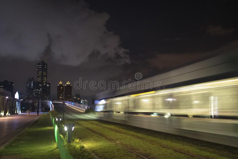 The view of LRT light rail transit in Kaohsiung City, Taiwan. When it passes at night. You can also see 85 Sky Tower far away in this photo royalty free stock photo