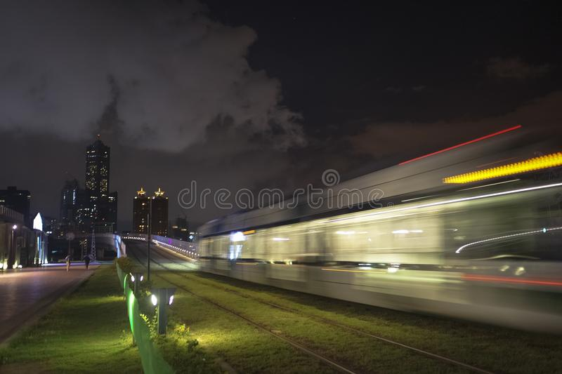 The view of LRT light rail transit in Kaohsiung City, Taiwan. When it passes at night. You can also see 85 Sky Tower far away in this photo royalty free stock photography