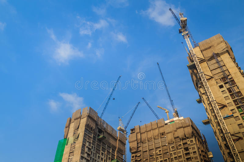 View of luffing jib tower crane at high rise building construction site project. Skyscraper building under construction with stock images
