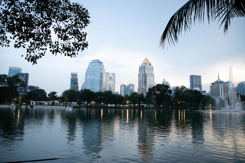 View of Lumphini Park lake with buildings in Bangkok with sunset light stock photo