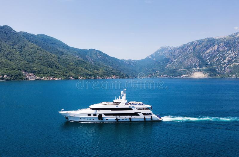 View on the luxury yacht in Montenegro. Blue sea water background from air. Mountains and sea landscape. Summer seascape from air. stock photography