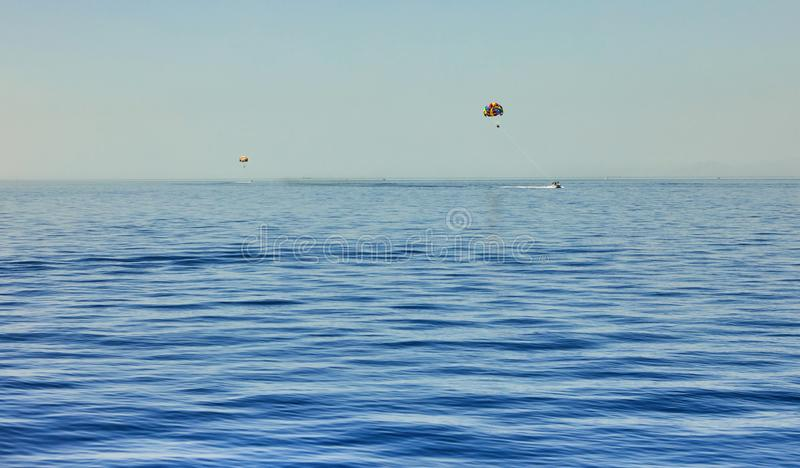 The view from the luxury yacht to the open red sea with the attraction flying on a parachute tied to a boat stock photography