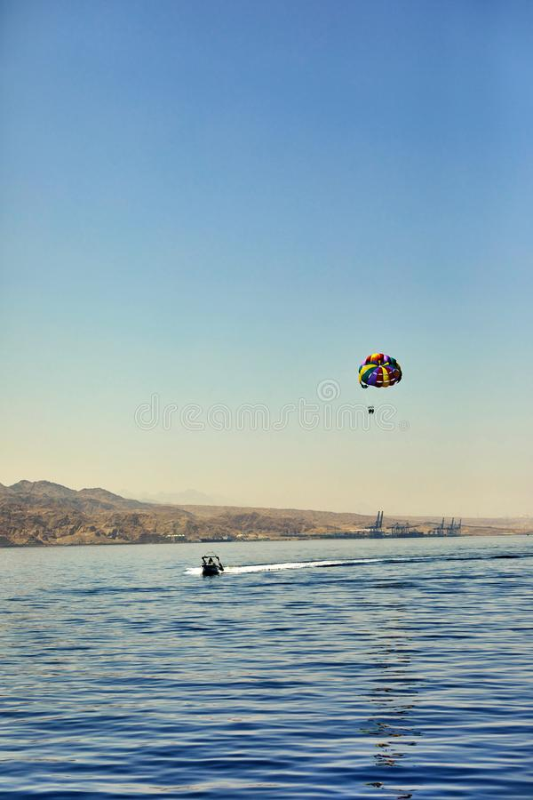 The view from the luxury yacht to the open red sea with the attraction flying on a parachute tied to a boat stock photo
