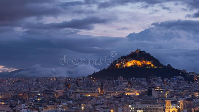 Lycabettus hill in Athens. View of Lycabettus hill from Areopagus hill in central Athens, Greece royalty free stock images
