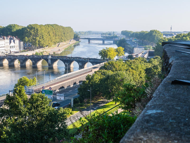 View of Maine River at Angers, France, on a summer day. Bridges span the Maine River at Angers, France, on a bright summer morning. Stone wall protecting the royalty free stock photo