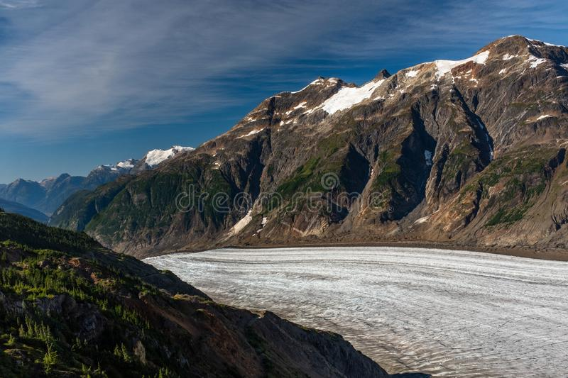 A view of the majestic Salmon Glacier as it dips down a gorge created by the the glacier in British Columbia, Canada, beautiful. Blue sky, nobody in the image stock photography