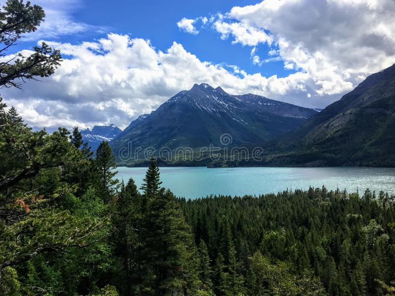 A view of a majestic turquoise lake surrounded by vast green evergreen forests and mountains on a sunny day with blue sky. royalty free stock images