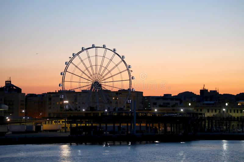 View of Malaga harbor with Ferris wheel at sunset, Malaga, Andalusia, Spain.  royalty free stock photos