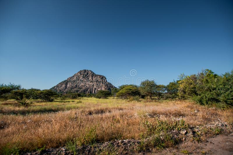 A view of the male hill at Tsodilo Hills, a UNESCO world heritage site featuring ancient San rock paintings. Pictured amid grassy. And arid plains stock photos