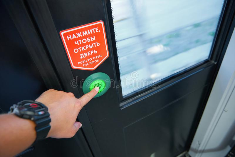 View of man hand pushing the door push button to make an unlock signal for local doors opening while train stops at a station. Pas royalty free stock photography