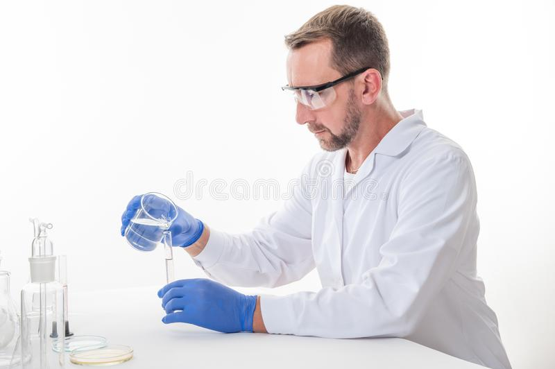 View of a man in the laboratory while performing experiments. Man in the laboratory, view of a man in the laboratory while performing experiments royalty free stock photo