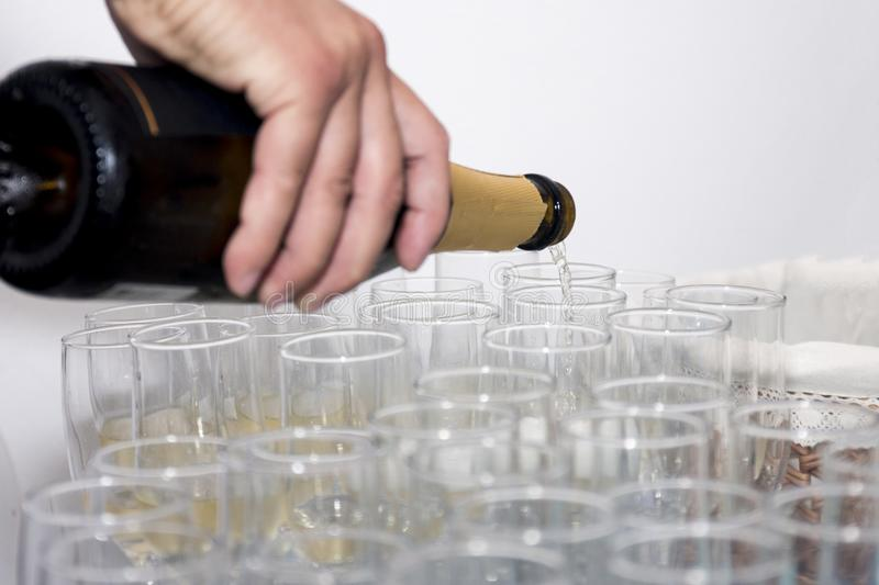 Pouring champagne. View of a man pouring sparkling champagne on glasses stock photography
