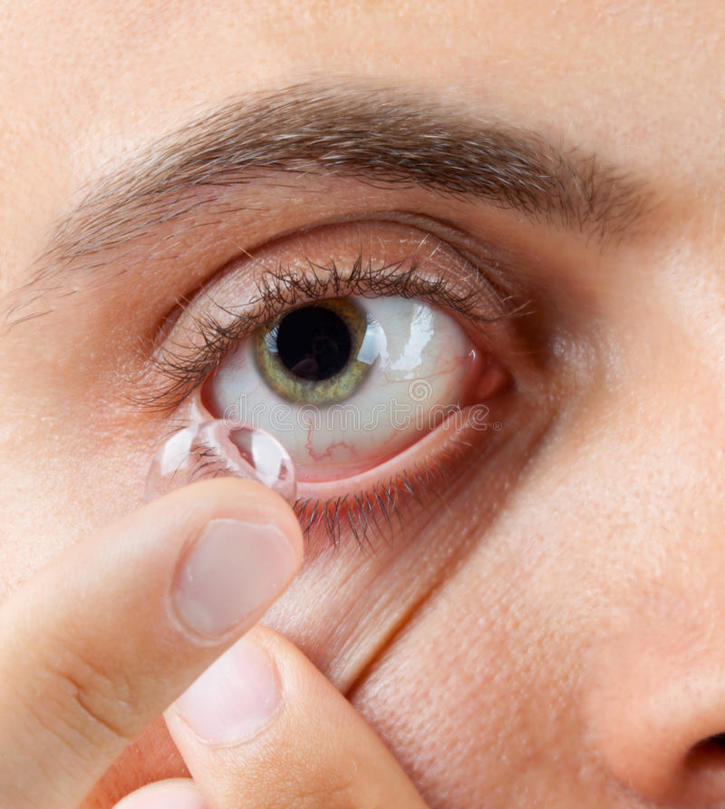 View of a man's green eye while inserting a corrective stock image