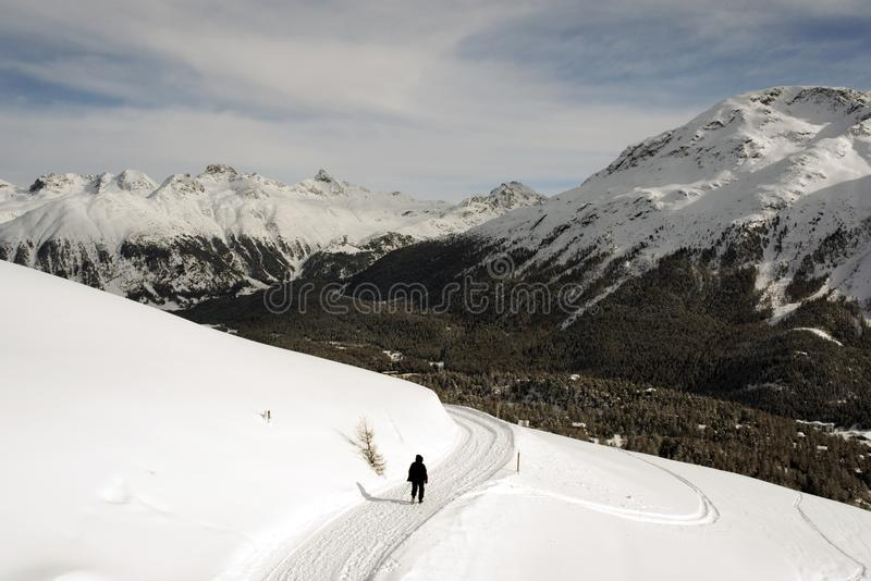 A view of a man walking in the snow covered landscape in the mountains in the alps switzerland.  royalty free stock images
