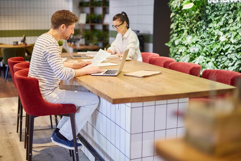 People studying and working in cafeteria. View of man and woman sitting with laptops and papers at table in cafeteria having big load of work stock image