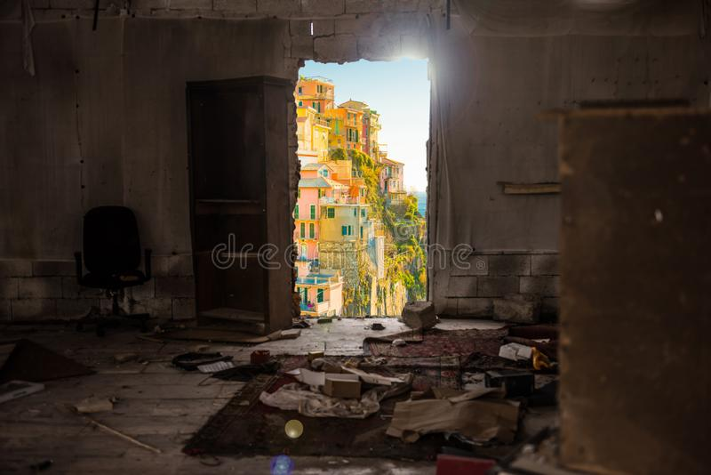View of Manarola, Italy. An old empty abandoned room with old furniture and clothes with an opened door with a vie of the city of Manarola, Italy part of the stock photo