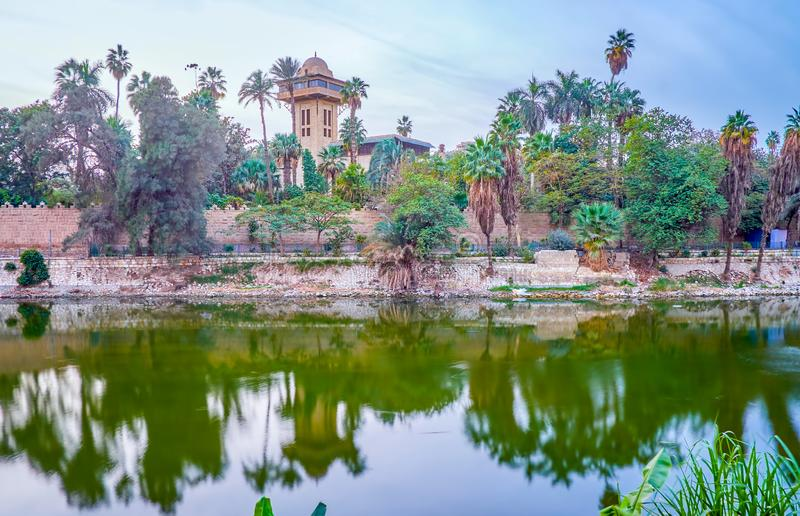 The Manial Palace museum on Roda Island, Cairo, Egypt. The view on Manial Palace lush garden behing the surrounding fence in Roda Island of Cairo, Egypt royalty free stock photography