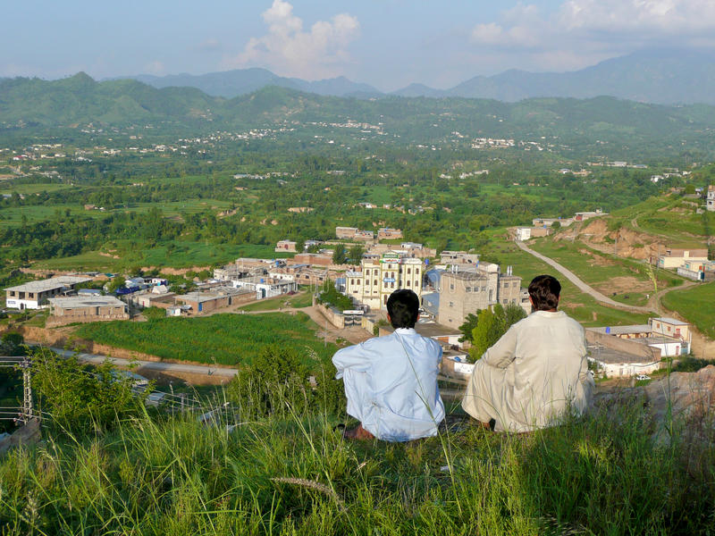 View of Mansehra in Northern Pakistan. Two men look out from a hilltop view on the valley and mountains around the Pakistani town of Mansehra, about fifteen stock images