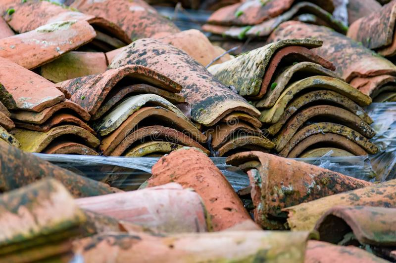 Stacked weathered red roof tiles on ground royalty free stock photos