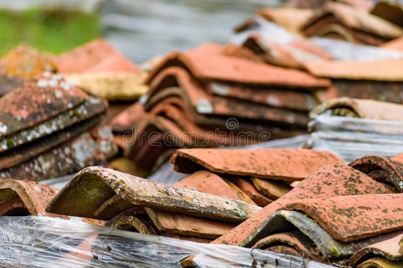 Stacked weathered red roof tiles on ground royalty free stock photography