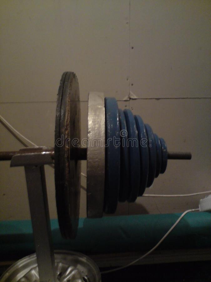 View of many weights on the end of a weightlifting bar in gym royalty free stock photos