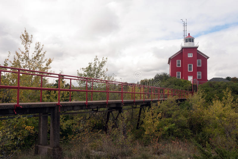 A view of the Marquette Harbor Lighthouse from the side the Lake Superior, Michigan, USA. Marquette Harbor Lighthouse: bridge for rescuers to Lake Superior royalty free stock photo