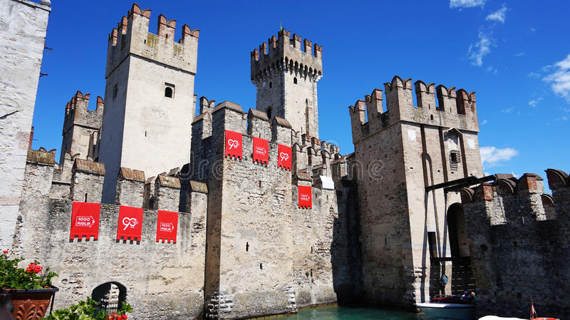 View of the medieval Scaliger Castle of Sirmione with signboard of italian Rally Mille Miglia and speedboat passing, Sirmione, Ita. SIRMIONE, ITALY - MAY 15 stock image