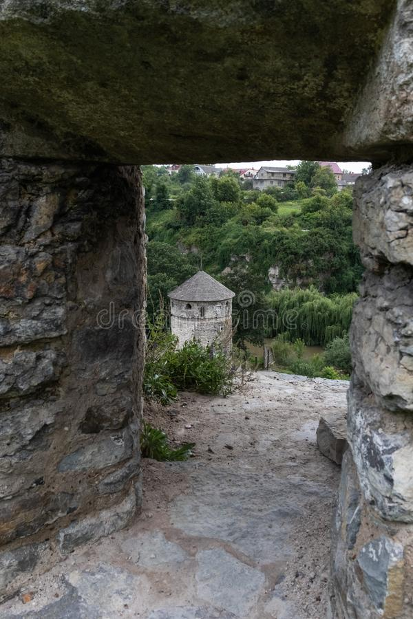 View of the medieval stone tower through the loophole in the stone wall. royalty free stock image