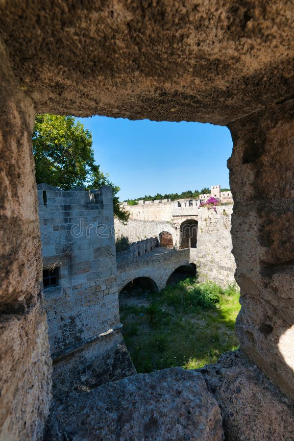 View through the Medieval walls Rhodes Town. Looking through a window in the medieval walls that surround the Medieval City of Rhodes. We can look down into the royalty free stock image