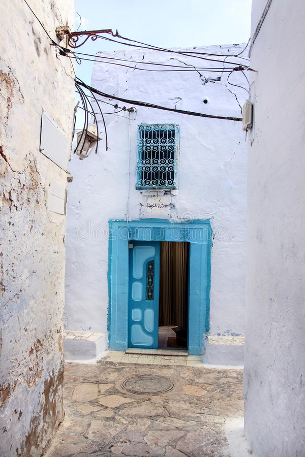 View of medina of tunisia old wall and wooden doors painted in blue and white on Mediterranean coast. stock image