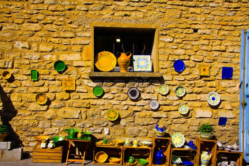 View on mediterranean colorful painted pottery plates hanging on ochre natural stone wall in natural sun light stock photos
