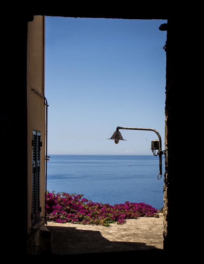 View of the mediterranean sea with flowers and a street lamp in a sunny day, Cinque Terre, Italy stock image