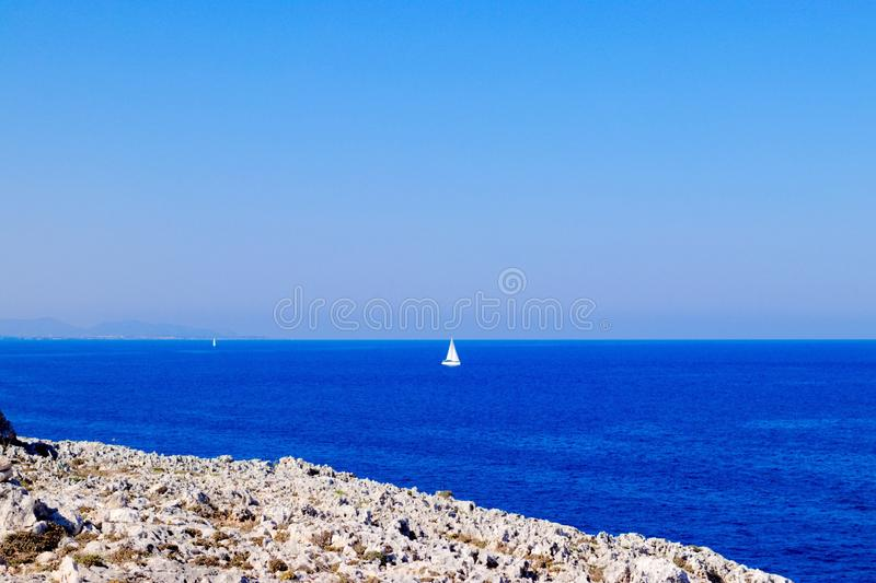View on the Mediterranean Sea with rocks in the front and a sailboat in the back royalty free stock images