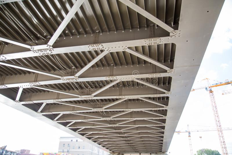 View of the metal beams of the bridge across the river from below on the background of construction cranes. stock photo
