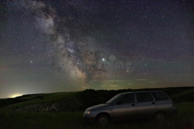 View of the Milky Way over the car travelers. Bright stars of the night sky. Astrophotography with a long exposure stock photography