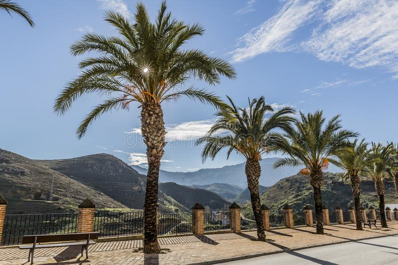 View of the Mirador Niña de Antequera with sidewalk with benches a small fence with metal bars, brick poles and palm trees royalty free stock photos