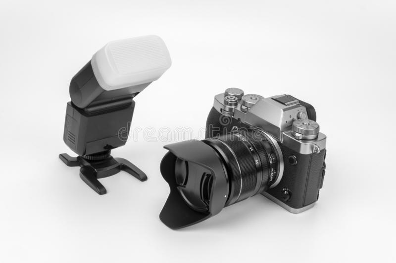 Mirrorless black Camera. View of a Mirrorless black camera isolated on a white background with a flash gun royalty free stock images