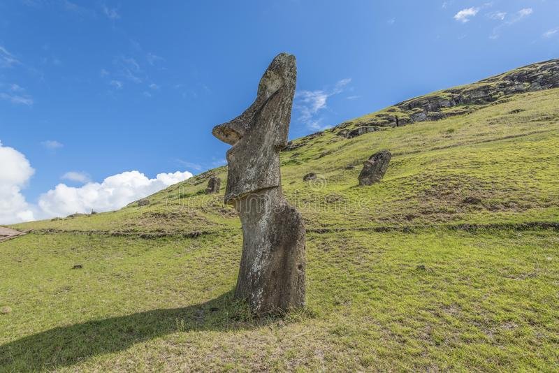 View of a moai in profile on the hill of the Rano Raraku volcano. Path on the hill of the moais of the Rano Raraku volcano where all the moai were sculpted stock photos